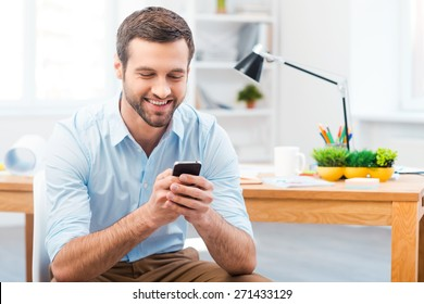 Staying in touch with his colleagues. Handsome young man holding mobile phone and smiling while sitting at his working place