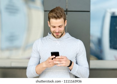 Staying in touch. Man with beard walks with smartphone, urban background. Guy use smartphone to send message stay in touch. Man typing text message smartphone. Send message concept.