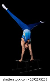 Staying up. Muscular male gymnast training in gym, flexible and active. Caucasian fit guy, athlete in blue sportswear doing exercises for strength, balance. Movement, action, motion, dynamic concept.