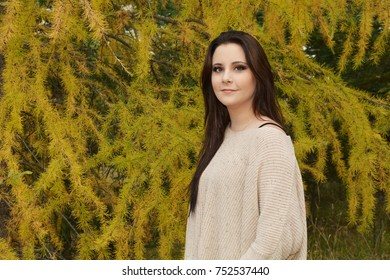 Staying warm in a cream colored sweater standing by a tamarack / larch tree in autumn