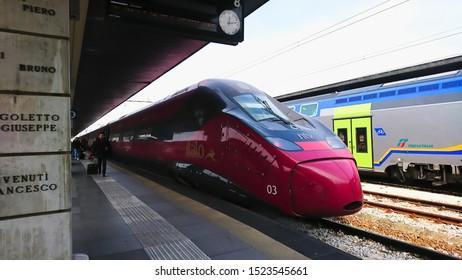 Stazione di Venezia Santa Lucia, Venice, Italy - April 9, 2018: passengers walking next to a modern locomotive of a train on the platform of Venezia Santa Lucia Railway Station from the front