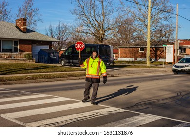 St.Catharines. Ontario/Canada-01.29.2020 Eighty year old crossing guard.  Older people always stay  young. Children cross the street after school. Follow the rules of the road. pensioners help childre