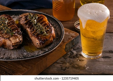 Steak and beer dinner for two with 2 honey marinated, grilled New York Strips topped with chimichurri in rustic wooden setting with fresh poured beer overflowing.