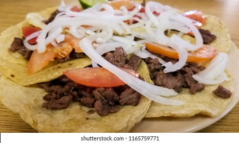 Steak bistec taco accompanied with onion, tomato, red sauce, avocado, lemon over a traditional tortilla. Typical Mexican food.