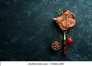 Steak with bone on a fork. Barbecue menu. Top view.