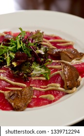 steak carpaccio with mushrooms and arugula salad drizzled with spicy mustard on a white plate