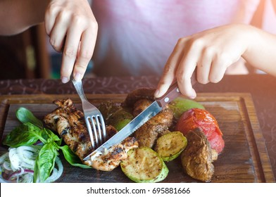 Steak of chicken with grilled vegetables are on a wooden board.