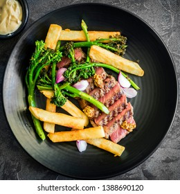Steak and chips with broccolini, wholegrain mustard, pickled shallots and bearnaise sauce.  Sliced porterhouse.