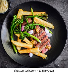 Steak and chips with broccolini, wholegrain mustard, pickled shallots and bernaise sauce.  Sliced porterhouse. Top view over slate.