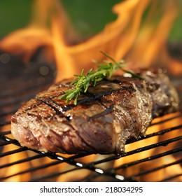 steak cooking over flaming grill