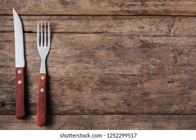 Steak fork and knife on wooden background