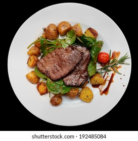 Steak with fried potatoes and spinach on wooden table