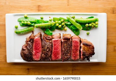Steak. Grade A, grass fed angus beef. Traditional classic New York steakhouse menu favorite. T-bone steak served medium to rare. Served with Peas  and seasoned with olive oil and salt and pepper.
