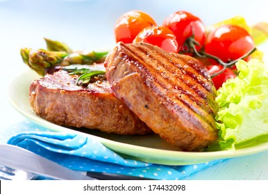 Steak. Grilled Beef Steak Meat with Vegetables - Asparagus, Cherry Tomato and Lettuce. Steak Dinner. Food
