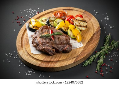 Steak with grilled vegetables on wooden plate
