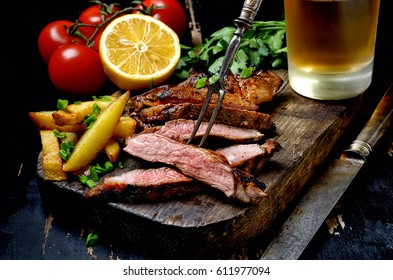 Steak with herbs and beer on a wooden background