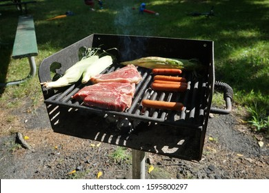 Steak, hotdogs, and corn cooking on an outdoor park charcoal grill