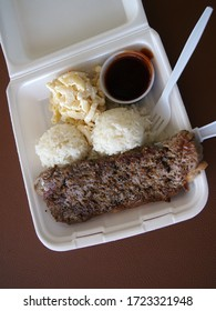Steak, mac salad, and two scoops of White Rice with red sauce in a Styrofoam plate local Hawaiian style plate lunch.