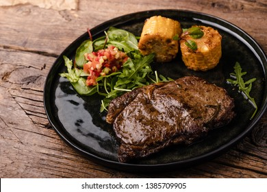 steak medium with grilled corn on a black plate and wooden table
