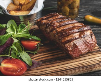 steak on the board with herbs, fried potatoes, spices on a black surface