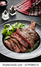 Steak on the bone. Rib eye. Tomahawk steak on the black plate with rosemary. Roasting - Rare. Entrecote.