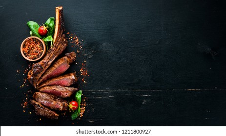 Steak on the bone. tomahawk steak On a black wooden background. Top view. Free copy space.