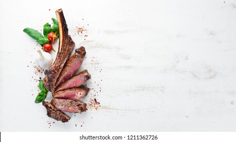 Steak on the bone. tomahawk steak On a white wooden background. Top view. Free copy space.