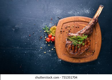 Steak on the bone. Top view. Free space for text. On a wooden background.