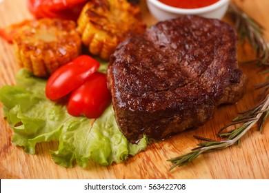 Steak on cutting board on wooden black rustic background