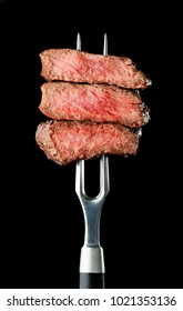 steak on fork isolated on black