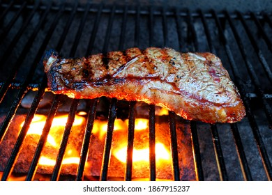 Steak on a grill, lighted from below, glowing orange, brown grill lines from cooked area on top.