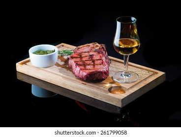 Steak on a wooden board with a glass of whiskey
