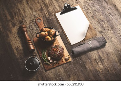 Steak on wooden serving board, with baked potatoes in a pot and sauce, with cliboard menu template, isometric view with copy space