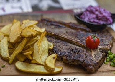 Steak with potato and salad served on a cutting board