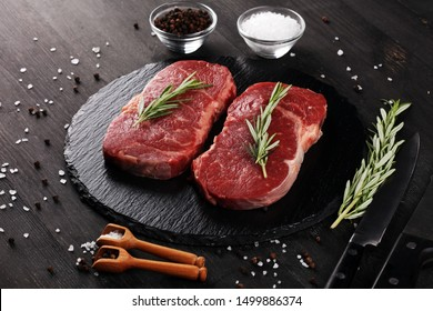 Steak raw. Barbecue Rib Eye Steak or rump steak on rustic table with rosemary