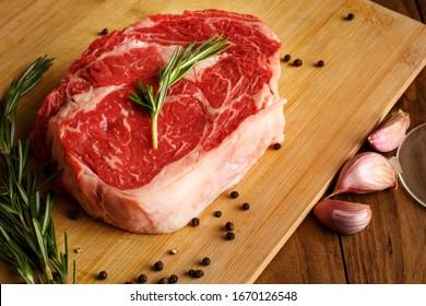 Steak Raw meat. Black Angus Prime meat steaks. Rib Eye Steak, dry Aged Wagyu Entrecote  Ribeye Steak with seasoning on dark wooden background. Top view. Rosemary leaves, Garlic, salt, pepper, red wine