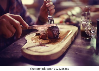 steak in the restaurant on the table / dinner in the restaurant, meat on the plate, served steak and cutlery