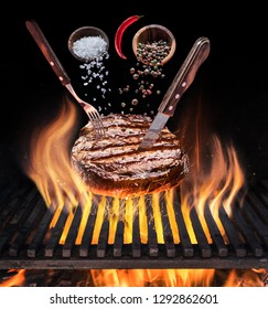 Steak ribeye cooking. Conceptual picture. Steak with spices and cutlery under burning grill grate.