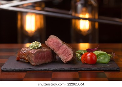 Steak rib-eye garnished with grilled vegetables on stone plate