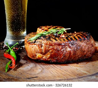 steak, rosemary and beer on a wooden background