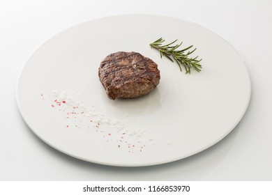steak with salt and rosemary on a plate isolated on white background.