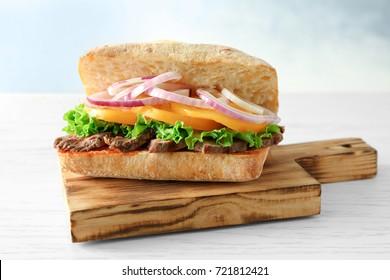 Steak sandwich on wooden board