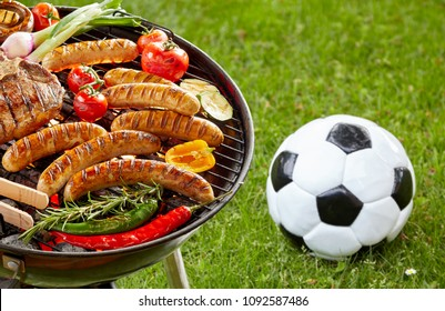 Steak, sausages and assorted fresh vegetables grilling on a barbecue outdoors on green grass with a soccer ball or football alongside and copy space in a conceptual sport image.