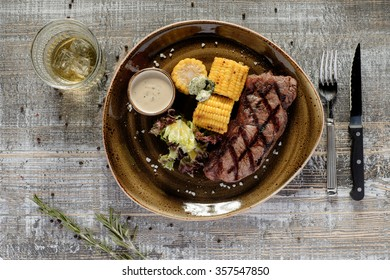 Steak served with corn and sauce. On wooden table with knife and fork.