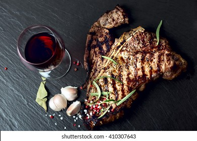 Steak with spices and glass of red wine on stone