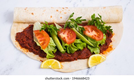 Steak tartar a la turca (Çiğ köfte) on lavash bread served with lemon, cucumber, tomato and coriander leaves in metal plate, isolated on white, closeup.