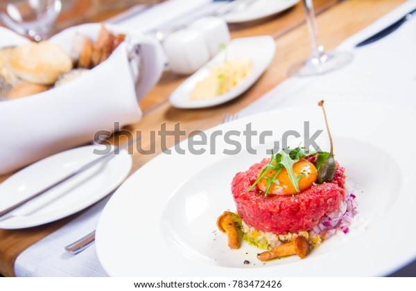 Steak tartare served in a restaurant with egg yolk,  onion, pickles, caper, mushroom and rocket salad