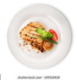 Steak with tomatoes in a white plate isolated