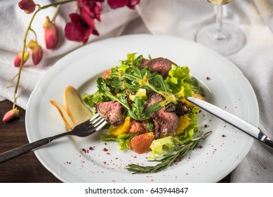 Steak with vegetables and a glass of wine on the table close-up. Meat and salad - Healthy fresh food.