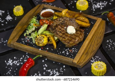 Steak with vegetables. Medium roast meat steak from pork, beef on the board